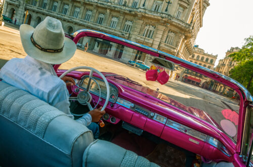 Taxi driver in a traditional hat driving a vintage car in Old Havana, Cuba.